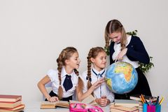 Three girls schoolgirls on the lesson of geography with a globe in school stock photos