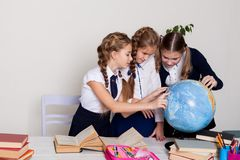 Three girls schoolgirls on the lesson of geography with a globe in school royalty free stock image