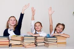 Two girls schoolgirls sit with books at his desk on the lesson at school royalty free stock photos