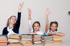 Two girls schoolgirls sit with books at his desk on the lesson at school royalty free stock image