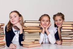 Two girls schoolgirls sit with books at his desk on the lesson at school royalty free stock photo