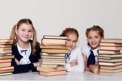 Two girls schoolgirls sit with books at his desk on the lesson at school stock photo