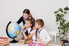 Three girls schoolgirls on the lesson of geography with a globe in school stock photo