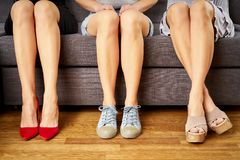 Three girls with legs sitting on the couch in different shoes and different styles on couch. Three girls with perfect legs sitting on the couch in different stock images