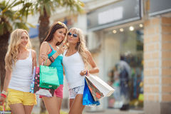 Three girls with shopping bags and go shopping. Stock Photos