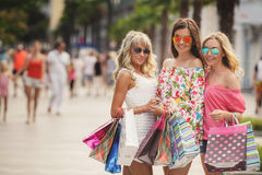 Three girls with shopping bags and go shopping. Royalty Free Stock Photography