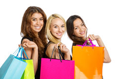 Three Girls with shopping bags. Girls with shopping bags over their shoulder on white background royalty free stock image