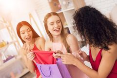 Three girls with shopping bags taking red ress out of bag. They are celebrating women`s day March 8. Three girls in red and white dresses with shopping bags royalty free stock images