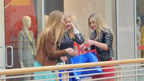 Three girls on a shopping: meeting friends. Slow. Two girls meet at his girlfriend shopping, show off to each other things. Slow motion stock video footage