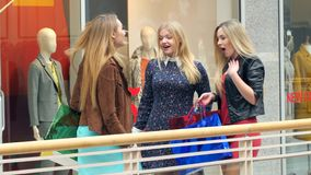 Three girls on a shopping: meeting friends. Two girls meet at his girlfriend shopping, show off to each other things stock video footage