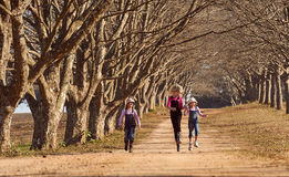 Three girls sisters running skipping down tree lined dirt road Stock Image