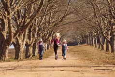 Three girls sisters running skipping down tree lined dirt road Royalty Free Stock Photos