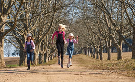Three girls sisters running skipping down tree lined dirt road Royalty Free Stock Photo