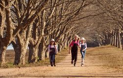 Three girls sisters running skipping down tree lined dirt road Royalty Free Stock Photography