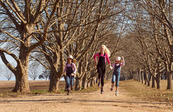Three girls sisters running skipping down tree lined dirt road Royalty Free Stock Image