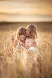Three girls sisters walk in field with rye sunset Royalty Free Stock Photo