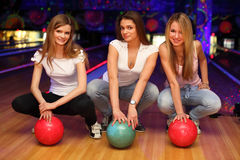 Three girls sit with balls in bowling club Stock Photo