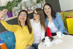 Three girls sit in a cake shop and photograph themselves with a smartphone stock photo