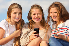 Three girls sit with mobile phones and smile Royalty Free Stock Photography