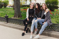 Three girls sit on the park background stock images