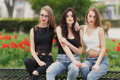Three girls sit on the park background royalty free stock photos