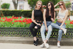 Three girls sit on the park background stock photos