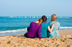 Three girls sitting. On a beach Stock Photography