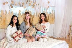 Three girls sitting on the bed in cozy sweaters, holding gifts Royalty Free Stock Images