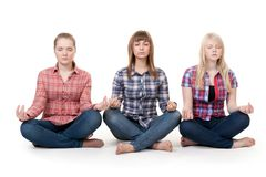 Three girls sitting in lotus posture Royalty Free Stock Photography