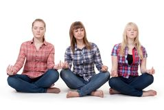 Three girls sitting in lotus posture Royalty Free Stock Photos