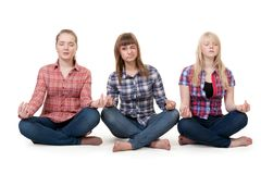 Three girls sitting in lotus posture Stock Photography