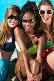 Three girls sitting on swimming pool in summer relaxing. African and Caucasian girls royalty free stock photo