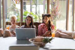 Three Girls Sitting At Table Use Laptop Computer Hold Cell Smart Phones, Young Woman Friends Together Stock Images