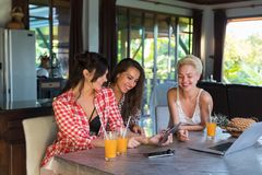 Three Girls Sitting At Table Use Tablet Computer Happy Smiling, Young Woman Friends Together Royalty Free Stock Photography