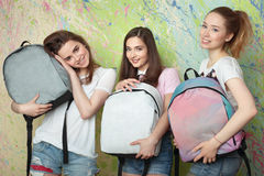 Three girls smiling and holding backpacks Stock Images