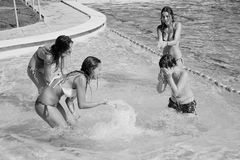Three girls splashing boy with water guns in pool black and white. Beautiful family teenagers in pool having fun Stock Photography