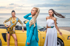 Three girls with sport car. On a beach Royalty Free Stock Photo