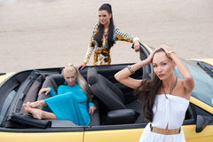 Three girls with sport car. On a beach Royalty Free Stock Photos