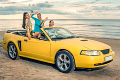 Three girls with sport car Stock Photos
