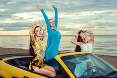 Three girls with sport car. On a beach Stock Images