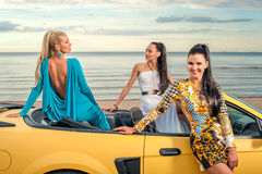 Three girls with sport car. On a beach Royalty Free Stock Images