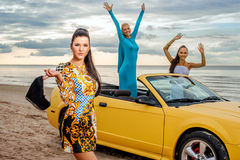 Three girls with sport car. On a beach Stock Image