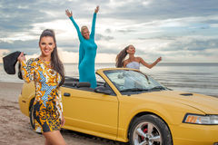 Three girls with sport car. On a beach Stock Photography