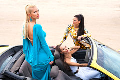 Three girls with sport car Stock Photos