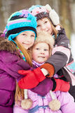 Three girls stand embracing each other in park Royalty Free Stock Photo