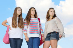 Three girls stand together. At background of blue sky with clouds Stock Photo