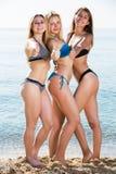 Three girls standing on beach Stock Images