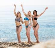 Three girls standing on beach Stock Photos