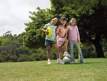 Three girls (7-9) standing on grass in park with frisbee, soccer ball and skipping rope, portrait stock images