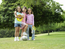 Three girls (7-9) standing on grass in park with frisbee, soccer ball and skipping rope, portrait stock photo